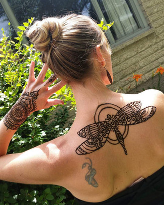 Dragonfly and hand tattoo