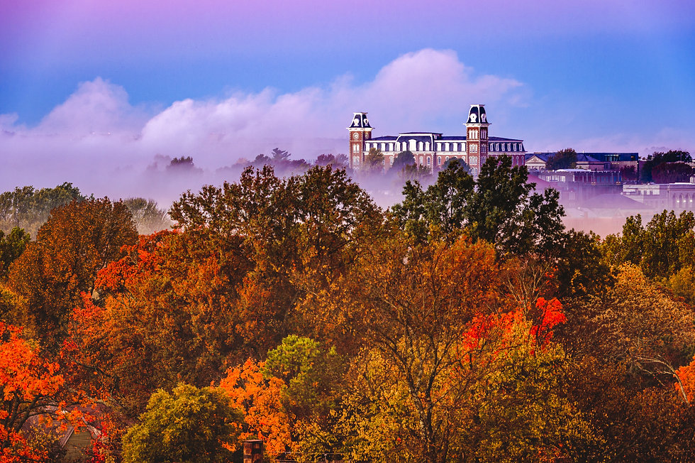 Fog blankets the fall foliage of the valley in front of a historical building in Fayettevi