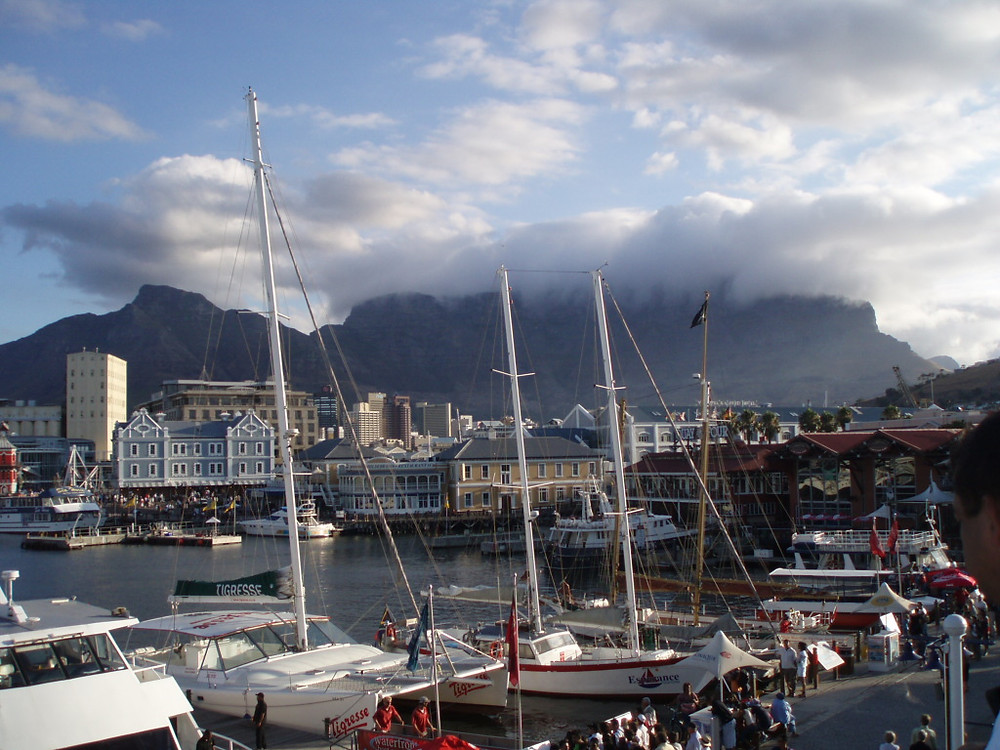 Photo from Table Bay Harbour with clouded mountains in the background. This is one of Cape Town's many tourist spots to include in your South Africa and Cape Town Itinerary. Table Bay is a place where to eat, drink, shop and party. Table Mountain surround the blue waters of the Table Bay.
