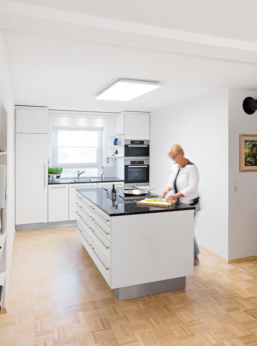 Weiße Küche mit dunkler Arbeitsplatte in ergonomischer Höhe