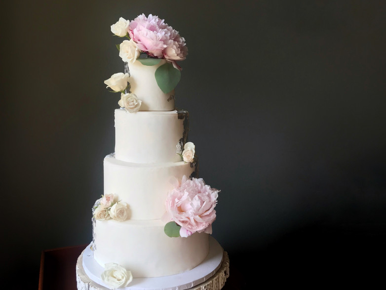 Fondant cake with fresh peonies and roses