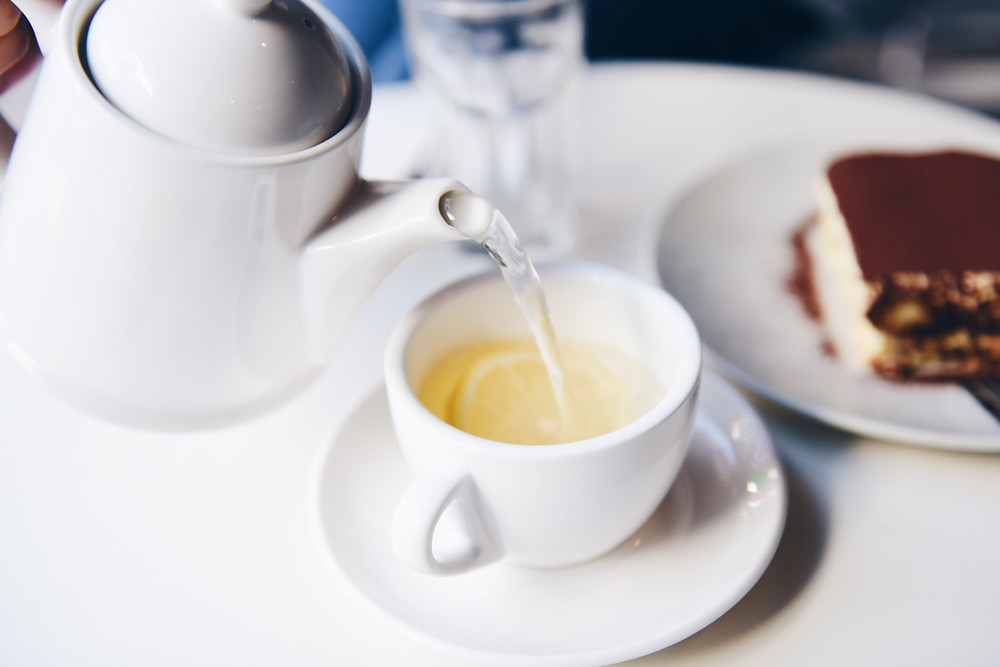 Tea being poured out of a white saucer into a ceramic white teacup with a fless slice of lemon, serived with a slice of tiramisu.