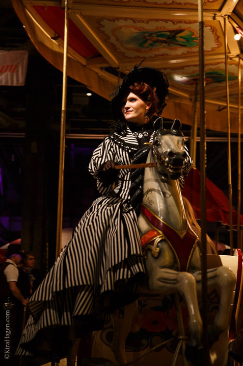 by Kira Hagen Photography  Model Oh, Marisha!  Taken at the turn-of-the-century Steampunk Fair in Bochum, 2018  The steampunk fair in Bochum is also an exciting event because there you can try out vintage amusement rides and see antique barrel organs. Riding an old carousel was as wonderful experience, as it was a very photogenic moment for a nice picture!