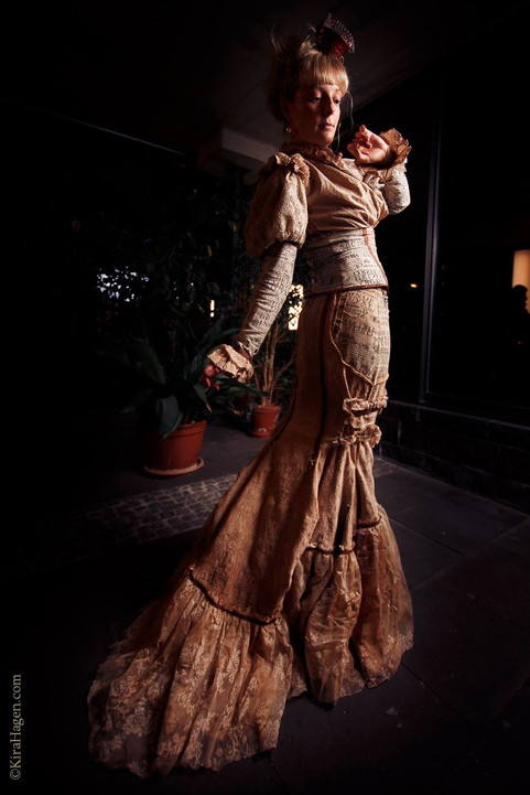 "Photo by Kira Hagen Photography  Model Cornelia Papendick  Taken in Cologne, March 2018 at Oh, Marisha! art exhibition opening  Originally, this dress was in light creamy colours, but I tea-stained it to achieve this fragile paperdoll look. She is fragile and as if wearing a paper dress, a steampunk doll is playful and unpredictable. This outfit consists of a few parts, only 2 are seen on this photo. I like costumes made of separate parts because it gives them more options of wear and different variations of styling. The skirt is a classic fishtail design but with a lot of layers in the ""tail"" part, so it gives the wearer a lovely feminine silhouette and a very attractive movement when worn."