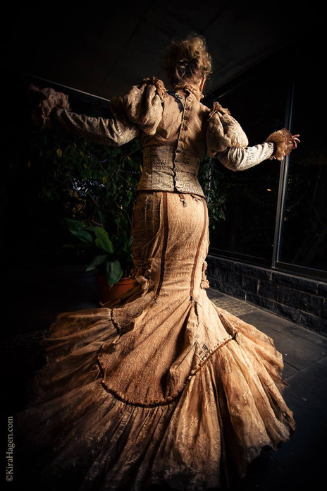 "Photo by Kira Hagen Photography  Model Cornelia Papendick  Taken in Cologne, March 2018 at Oh, Marisha! art exhibition opening  Originally, this dress was in light creamy colours, but I tea-stained it to achieve this fragile paperdoll look. She is fragile and as if wearing a paper dress, a steampunk doll is playful and unpredictable. This outfit consists of a few parts, only 2 are seen on this photo. I like costumes made of separate parts because it gives them more options of wear and different variations of styling. The skirt is a classic fishtail design but with a lot of layers in the ""tail"" part, so it gives the wearer a lovely feminine silhouette and a very attractive movement when worn. The skirt has a few hidden metal details, which look decorative when unused, however do allow attachments of additional skirt pieces for more options of wear. Please contact me for details."