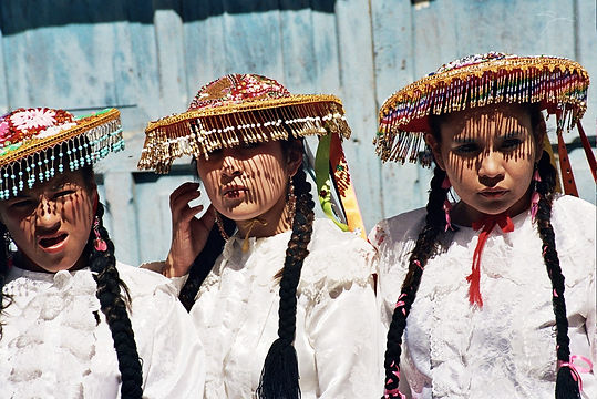 Three young Quechua girls wearing beaded traditional hats