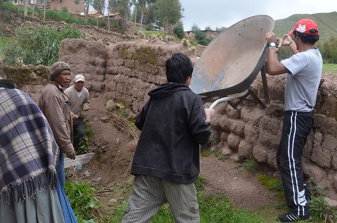 Mosqoy volunteers lowering wheelbarrow