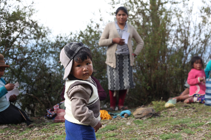 Young Quechua boy staring at camera with mother in background