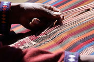 Weaver pulling a bunch of strings from a partially-woven textile