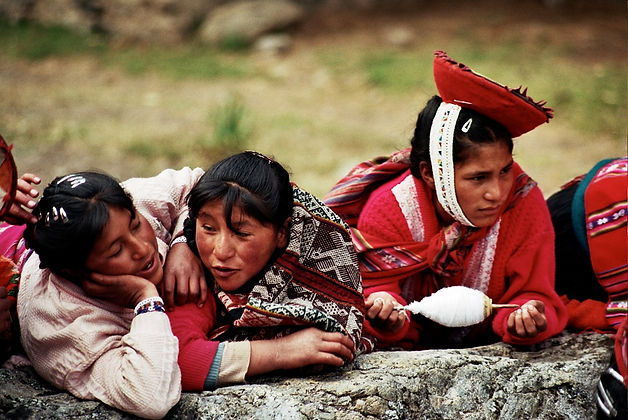 Three Quechua women, one is holding the pushka, the traditional spinning tool for making yarn