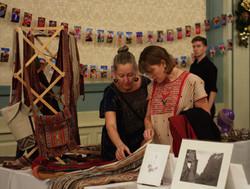 Two women examining textiles