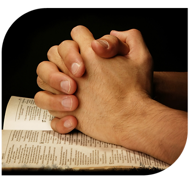 Hands clasped on Bible Praying