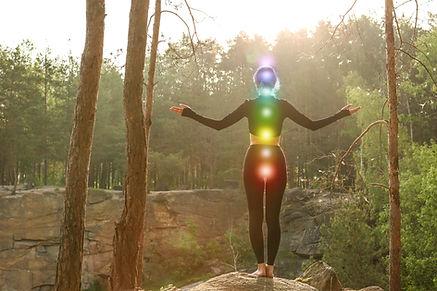 Woman with colorful chakras meditating i