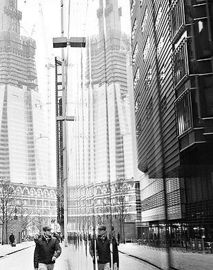 A man walking by a London Skyscraper