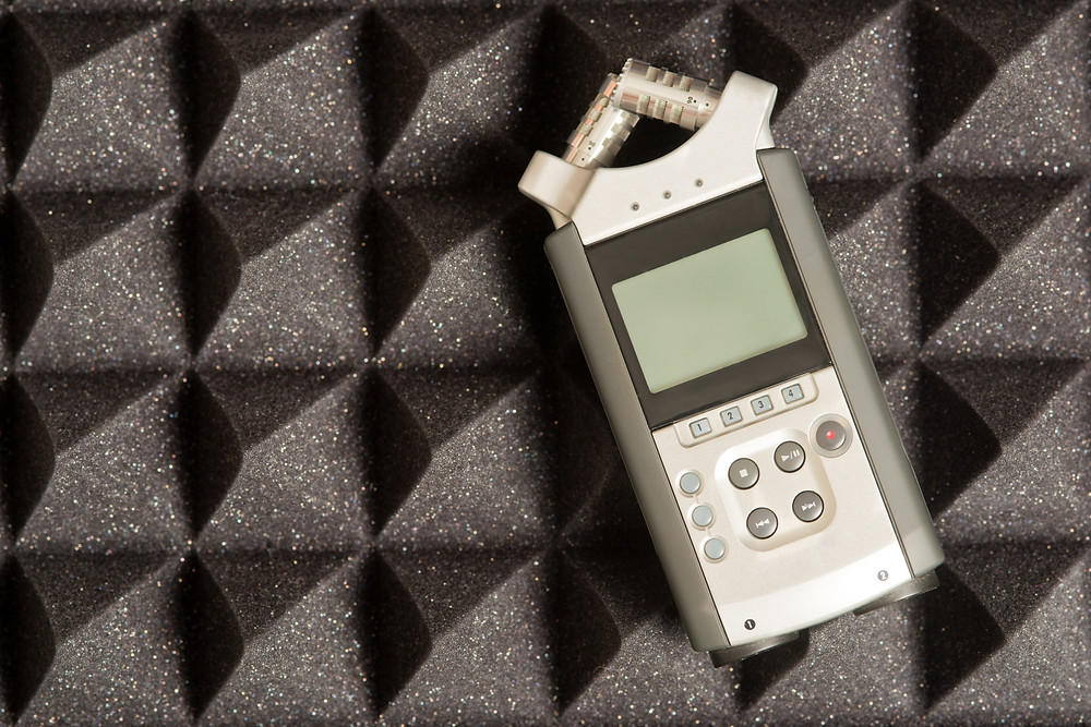Zoom audio recorder and dictaphone resting on sound insulation.
