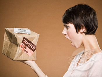 Woman holding crushed cardboard box with fragile label