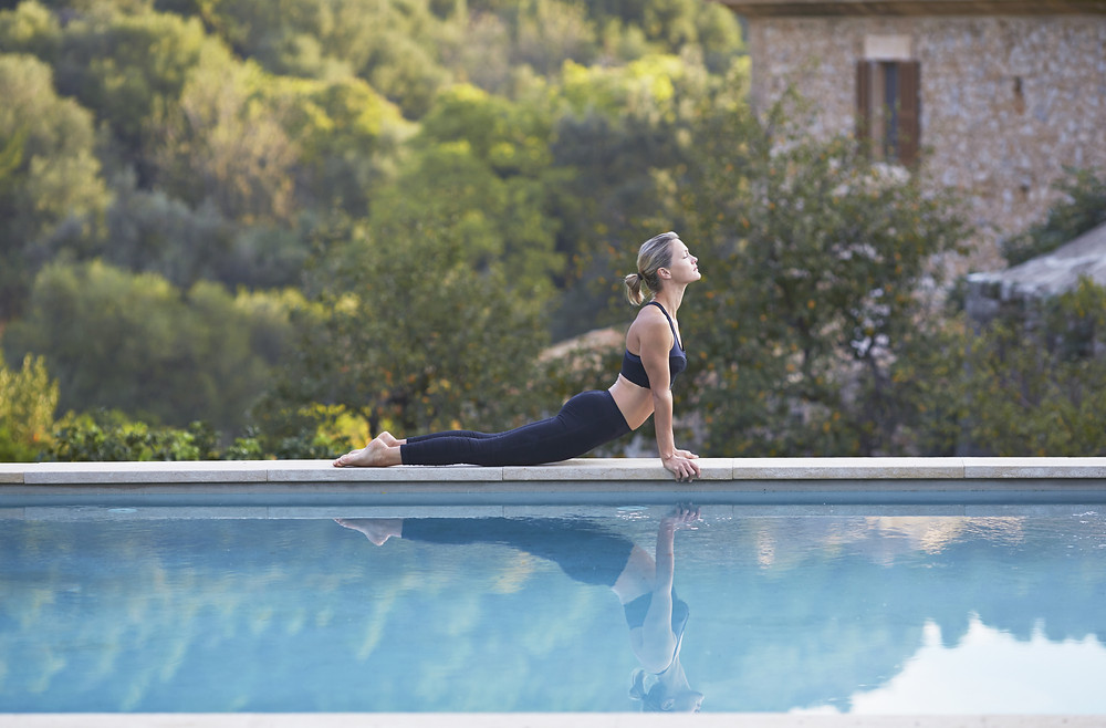 lady by the pool performing yoga poses.