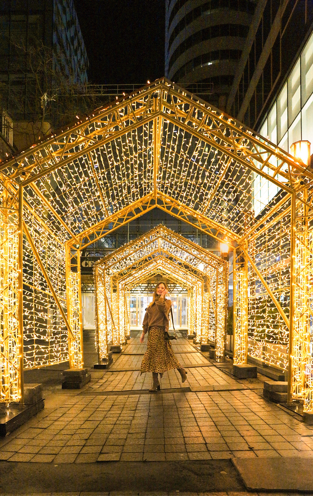 girl posing under cascade of lights by Toronto Eaton Centre
