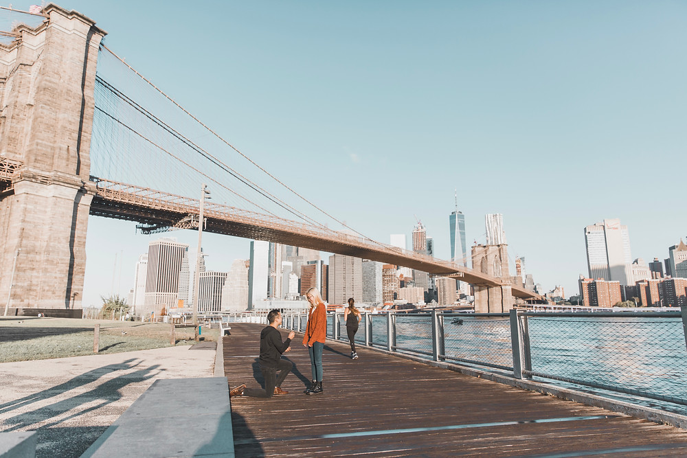 A man proposing to his girlfriend under the Brooklyn Bridge in New York.