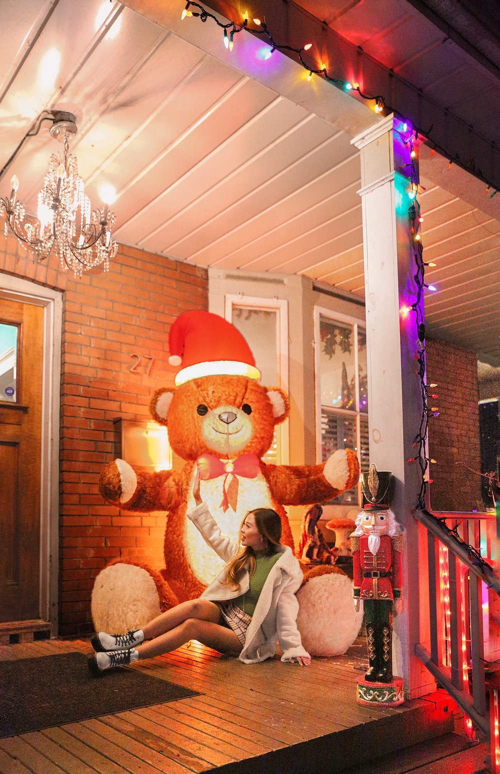 Girl sitting on porch next to oversized teddy bear