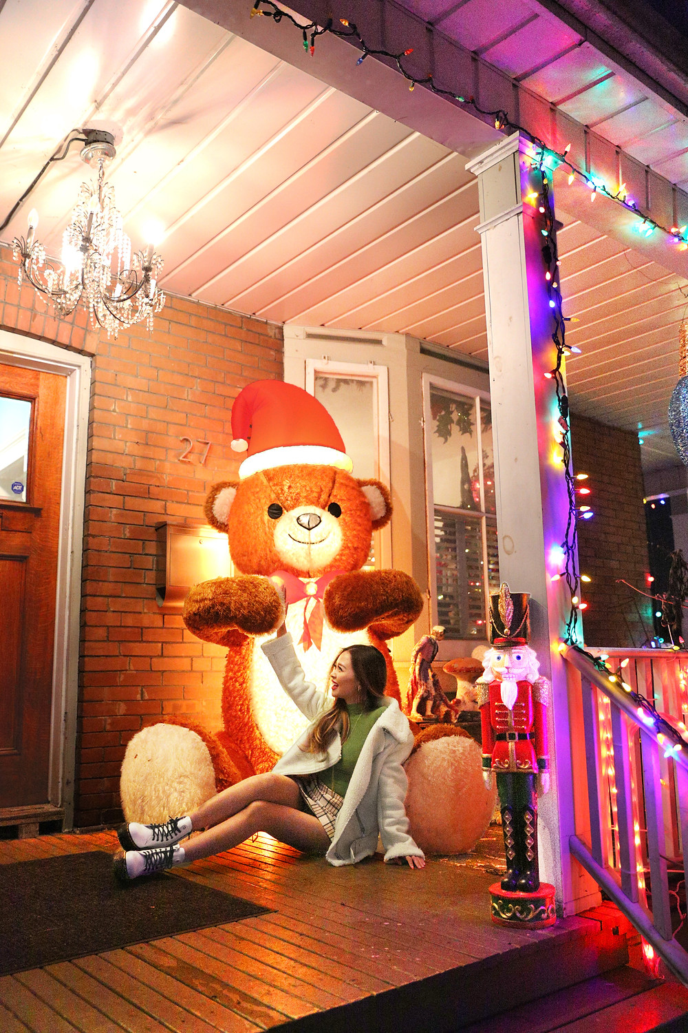 Girl sitting on front porch with oversized teddy bear