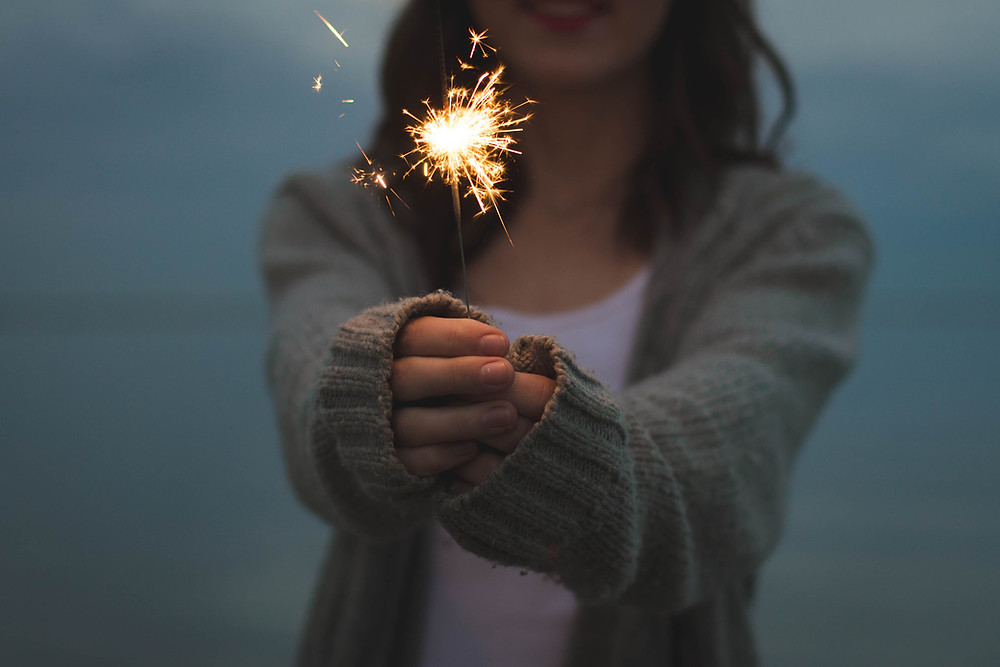 girl in cardigan holding sparkler by the beach