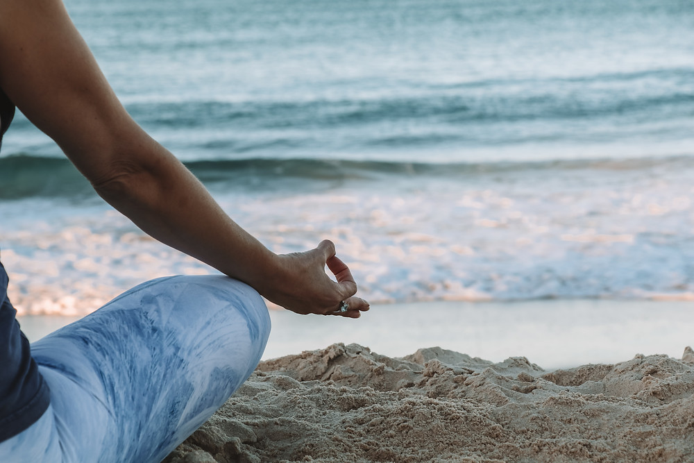 girl meditating by beach in a traditional pose