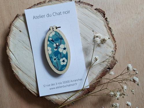 Broche ovale fleurs fond bleu clair