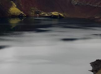 Les eaux sombres d'un lac de cratère, au coeur de l'Islande