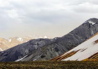 Le Mont Bláhnúkur au premier plan, essentiellement constitué de résinite, lui donnant sa couleur gris-vert
