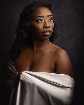 Beautiful black woman in a silver silk wrap with studio lighting