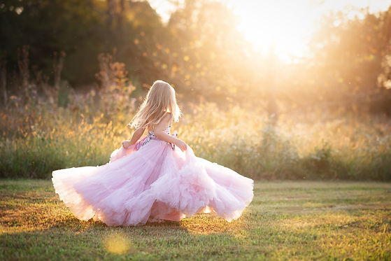 Blonde girl golden light sunset. Twirling in a couture dress