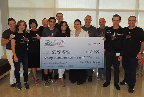 With proceeds from the 2017 memorial golf tounament, the Luke Tatsu Johnson Foundation presented a check to its beneficiary, Save Our Sick Kids.