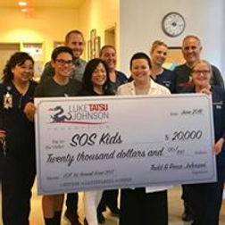 The Luke Tatsu Johnson Memorial Foundation presenting a $20,000 check to Dr. Tempe Chen and the Save Our Sick Kids Foundation.