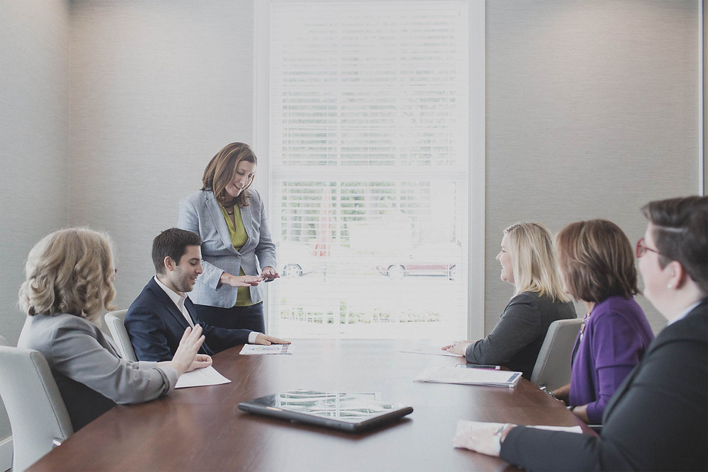 Simply Strategy employees gathered around a conference table, listening to Dorothy Carlin speak