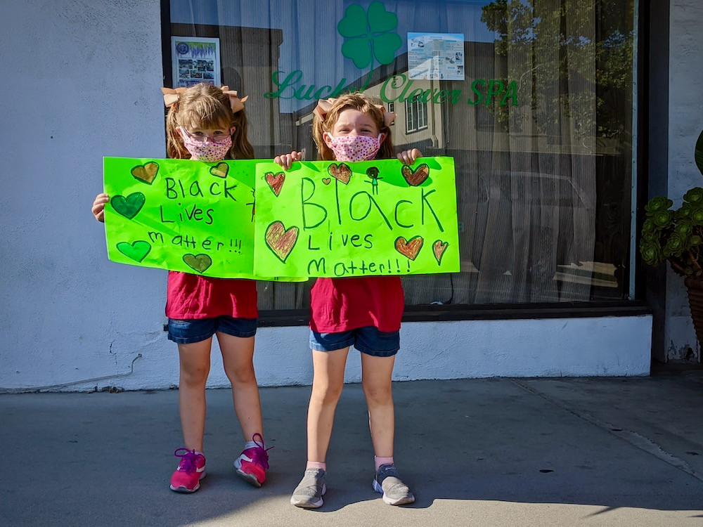 "Two little girls holding handmade signs saying, ""Black Lives Matter!!!"""