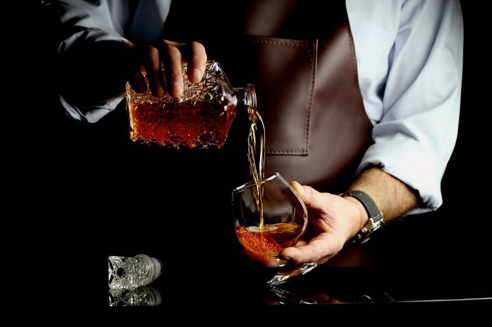 le barman réalise un cocktail a base de cognac