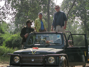 tourists look for tigers with their guide and jeep