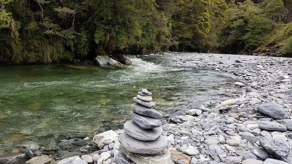 stacked rocks by rushing river
