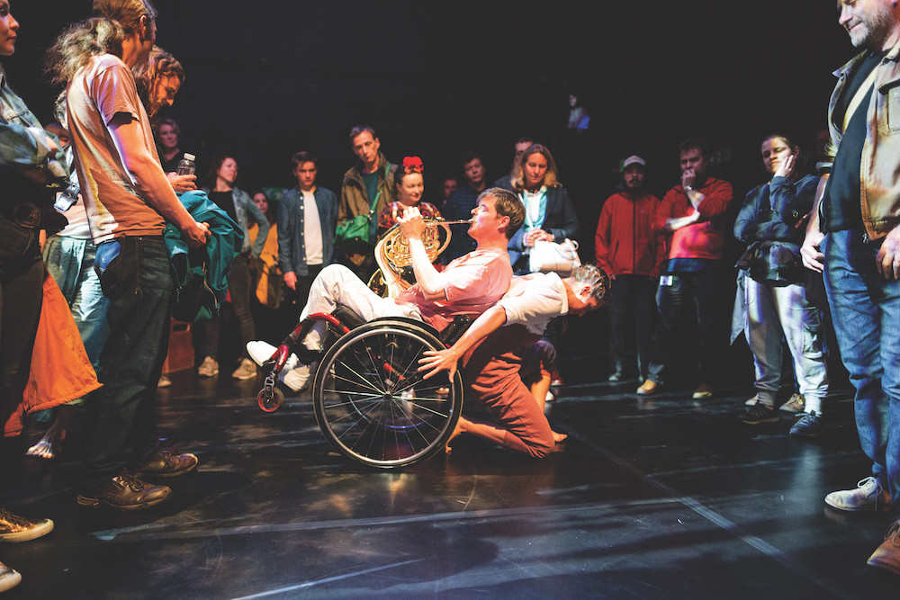 In a dark stage space, an audience stands in a broken circle around male french horn player in a wheelchair, wearing white trousers and shoes and a pink shirt, tipped back against a female dancer crouching on her knees in a white shirt and pink trousers. the audience members are wearing colourful clothing and look relaxed and happy.
