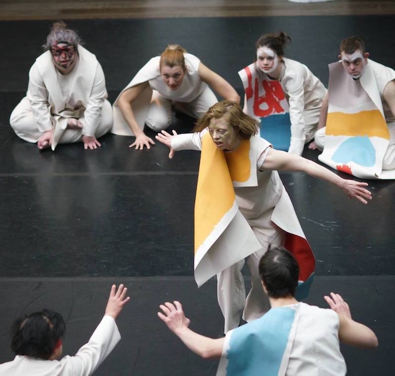 A circle of dancers in white clothing and brightly coloured paint crouch in a circle on black dance flooring, surrounding the lead dancer who dances in the middle with her arms outstretched.