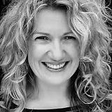 A black and white headshot of Joanne Roughton-Arnold smiling broadly at the camera, curly long hair framing her face