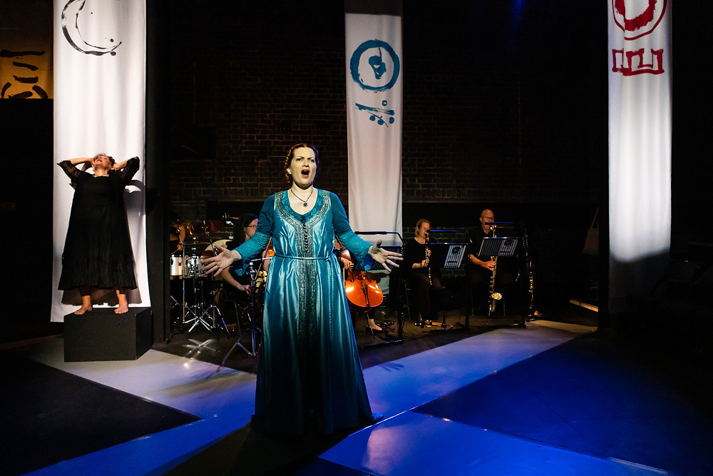 A stage scene with three large white banners with abstract symbols in black, blue and red. A small chamber orchestra plays in front of them. On the floor is a large white letter  X. At its centre is a white woman singing in a blue dress, with her arms outstretched. On the left, in front of one of the banners, is a Cuban dancer dressed in a flowing black dress, looking to the ceiling with her hands on her head.