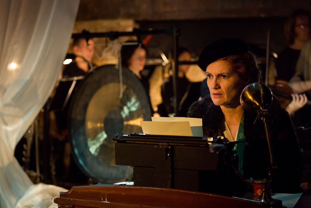 Joanne Roughton-Arnold as Iris. She wears a black beret and a green kimono robe over a white nightdress. She sits at a typewriter, staring into the distance in horror as she remembers past events. An ensemble of musicians is playing in the background.