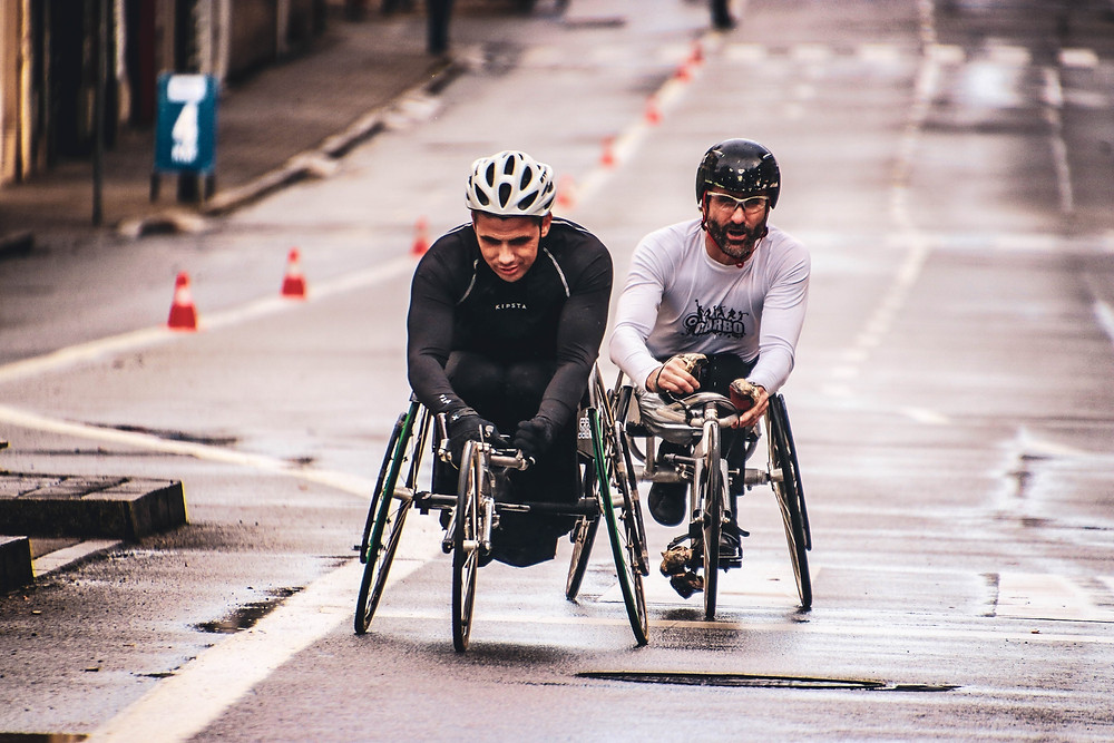 Two elite athletes in assistive cycles, racing on a rainy street. ont he left is a mixed race man in a black racing suit and white helmet. on the left and slightly behind him is a white man with a beard in a white racing suit and black helmet.