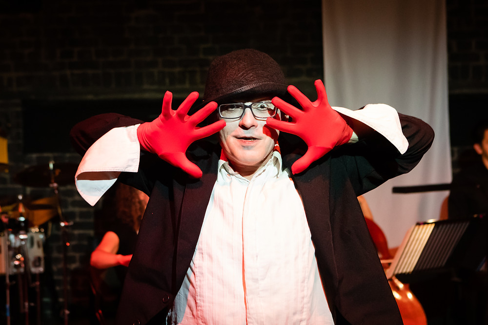 A man in white face paint, dressed in a shabby black tailcoat with a bowler had, white hirt and bright red gloves stares directly at the camera with a half smile on his face, with his hands splayed either side of his face. There are orchestral musicians onstage behind him.