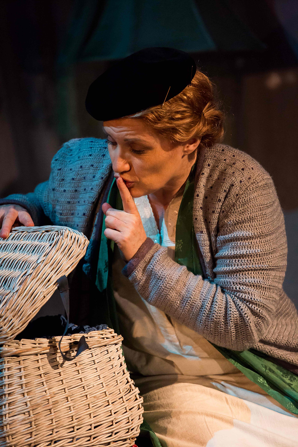 Joanne Roughton-Arnold as Iris. She is sitting next to a white wicker sewing basket, gently lifting the lid and putting her left index finger to her lips in a gesture to quieten the baby she imagines is in the basket. Her copper hair is twisted into a low bun under a black beret. She wears a grey cardigan over a green kimono robe and white nightdress