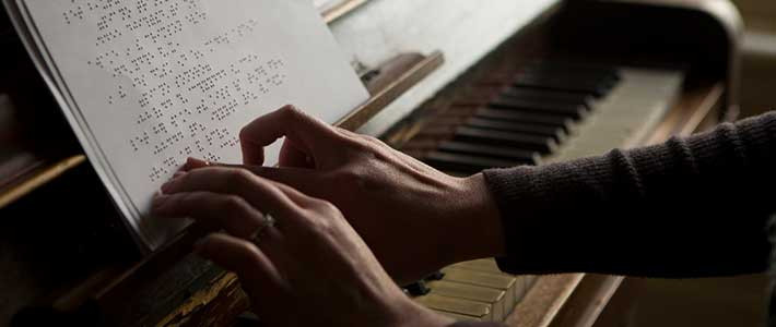 A closeup of a woman's arms in a brown cardigan, with an engagement ring on her left hand, touching braille sheet music at the piano.