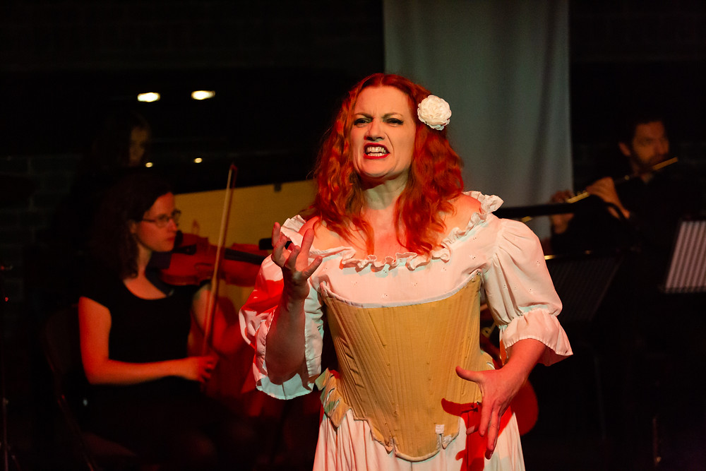 Singer Joanne Roughton-Arnold, dressed as Colombine, sings to the audience with a grimace. She has a white flower in her hair and her right hand is raised angrily. The image was taken during formidAbility's semi-staged performance of Schoenberg's Pierrot Lunaire for the 2019 Grimeborn Festival.