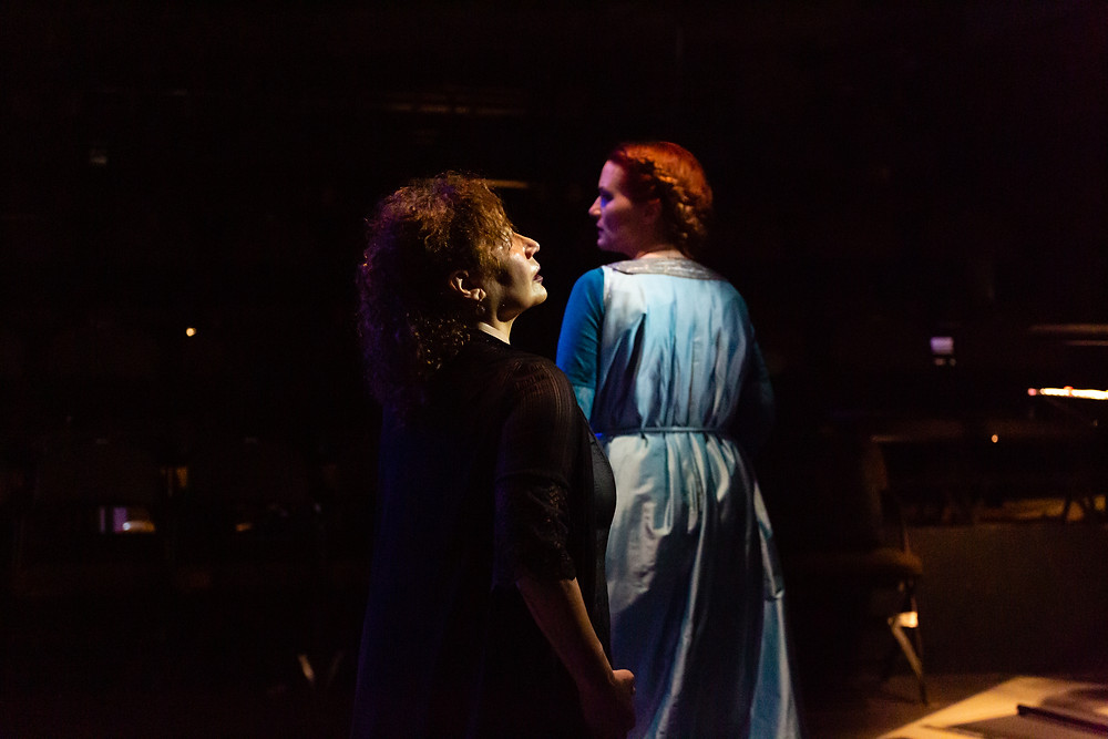 In the foreground of a dark stage is a Cuban woman dressed in black with dark curly hair. Her She is standing in profile, with her eyes raised to the lights. Behind her is a white woman with red hair in plaits, wearing a blue dress. her back is to the camera, and her head is turned to the left in profile. She looks anxious.